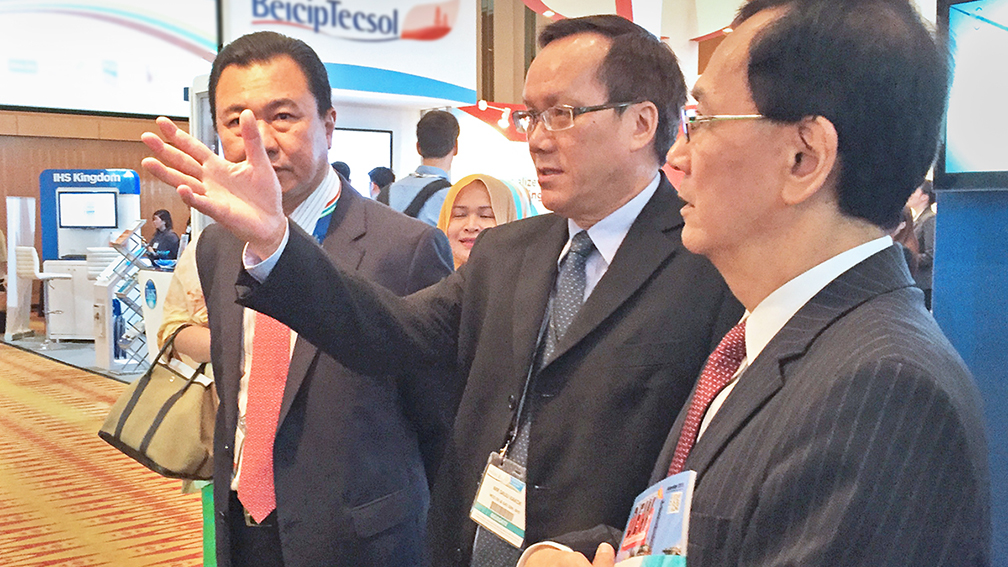 Sauu Kakok (center), VP of Hess Asia Pacific, gives a tour of the Hess booth to PETRONAS' visiting officials